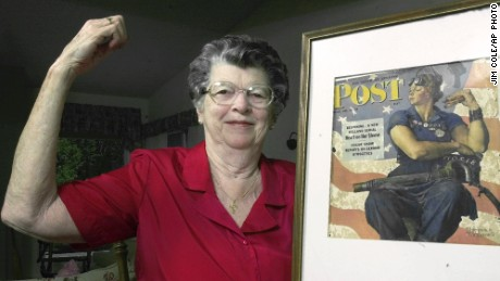 "Mary Doyle Keefe poses with the 1943 cover of the Saturday Evening Post for which she had modeled as ""Rosie the Riveter"" in a Norman Rockwell painting."