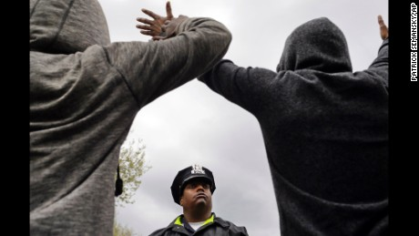 A member of the Baltimore Police Department stands guard outside of the department's Western District station as men hold their hands up in protest April 22.