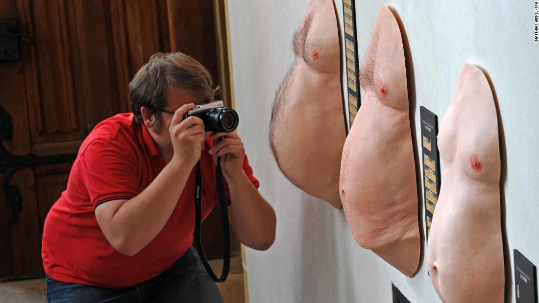 "A man photographs the average beer bellies of the Saxons, left; the Germans, center; and the Hessians in a new exhibit Friday, April 17, in Meissen, Germany. The exhibit, ""Prost! 1,000 Years of Beer in Saxony,"" is on display at the Albrechtsburg until November."