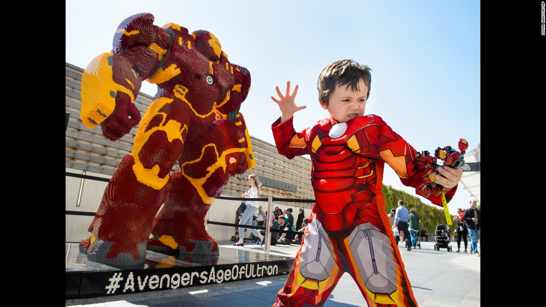 A boy dressed as Iron Man poses in front of a Lego statue of the superhero Tuesday, April 21, in London's Westfield Shopping Center. The Lego statue is more than 8 feet tall and weighs a ton. It took six professional builders 960 hours to create.