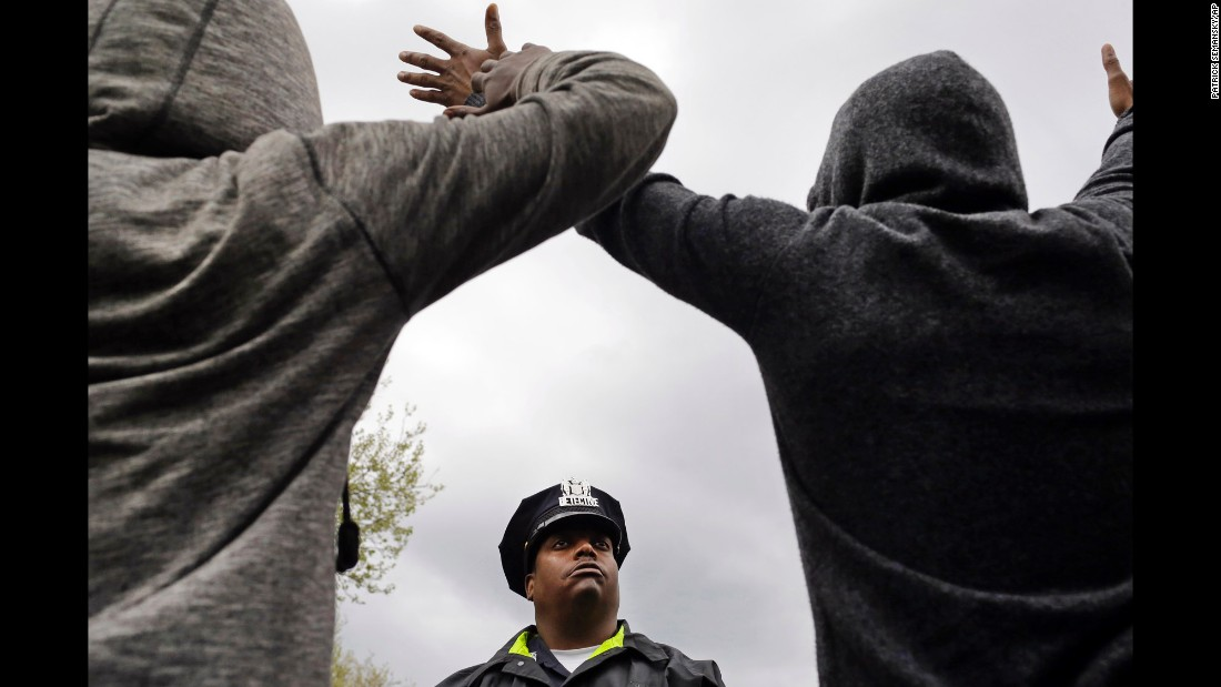 "A member of the Baltimore Police Department stands guard outside the department's Western District station as men hold their hands up in protest on Wednesday, April 22. <a href=""http://www.cnn.com/2015/04/22/us/baltimore-protests-freddie-gray-five-questions/index.html"" target=""_blank"">Protests are gaining steam in Baltimore</a> after a man died from a devastating injury he allegedly suffered while in police custody."