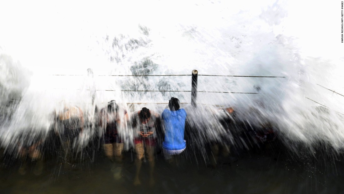 People withstand large waves on the San Blas beach in La Libertad, El Salvador, on Sunday, April 19.