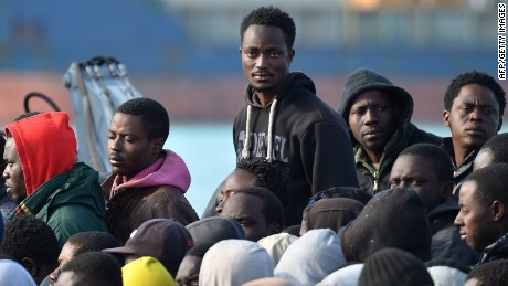 Rescued migrants stand as they disembark off the Italian Guardia di Finanza vessel Denaro at the Sicilian harbour of Catania on April 23, 2015. Calls have mounted for a military response to the Mediterranean migrant crisis, but experts say such plans are totally unworkable and mark an attempt to militarise what should be a purely humanitarian problem. European leaders will gather in Brussels to discuss new strategies in the wake of the latest disaster on April 19, in which hundreds of migrants drowned when their boat capsized on the way from Libya to Italy. AFP PHOTO / ALBERTO PIZZOLIALBERTO PIZZOLI/AFP/Getty Images