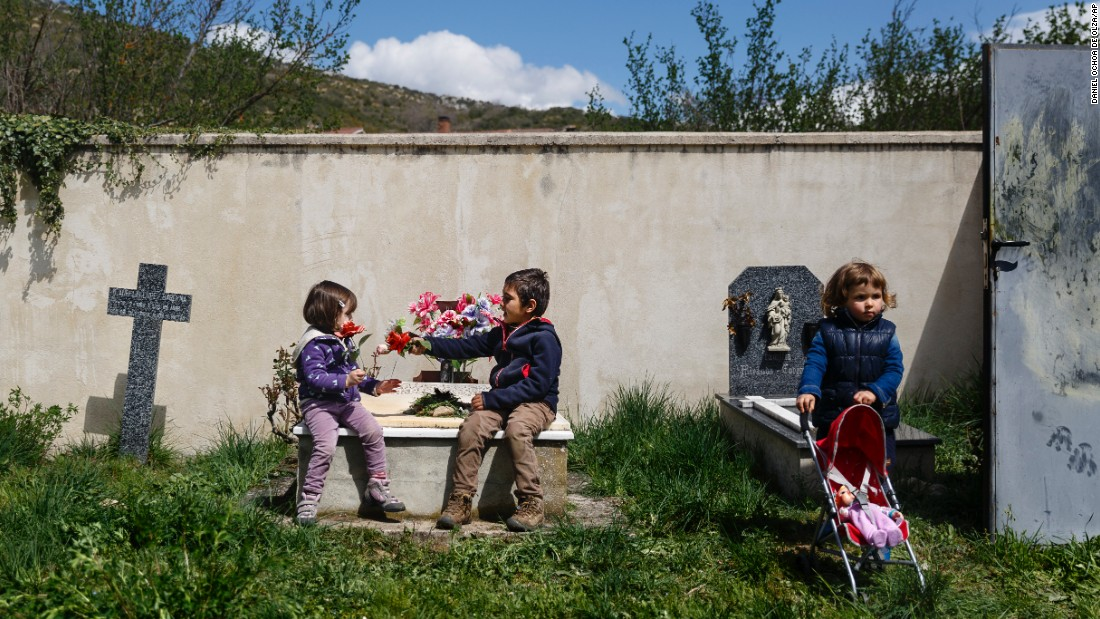 A boy gives a flower to a girl while sitting on a tomb in Valdenoceda, Spain, on Saturday, April 18.