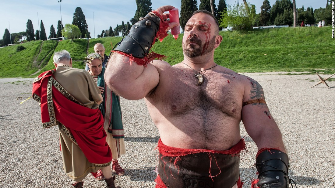 An actor dressed as an ancient gladiator puts fake blood on himself as he gets ready for a parade marking Rome's anniversary on Sunday, April 19.