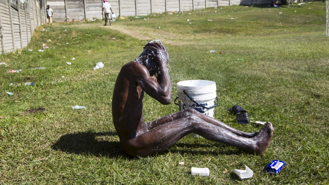 "A man bathes on a sports field Tuesday, April 21, in Durban, South Africa, adjacent to a camp for those affected by anti-immigrant violence. South Africa has deployed its army in ""volatile areas"" to curb a wave of anti-immigrant violence that has killed at least seven people this month, the defense minister said."