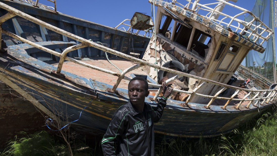 "Eric Joseph, a migrant from Nigeria, stands in a ""boat graveyard"" by the port in Lampedusa, Italy, on Wednesday, April 22. Joseph left Libya on a vessel and spent 21 hours at sea before being picked up by the Italian Coast Guard and brought to Lampedusa. <a href=""http://www.cnn.com/2015/04/21/world/gallery/europe-migrant-crisis/index.html"" target=""_blank"">Hundreds of migrants are believed to have died this month</a> as they attempted to cross the Mediterranean Sea to seek refuge in Italy."