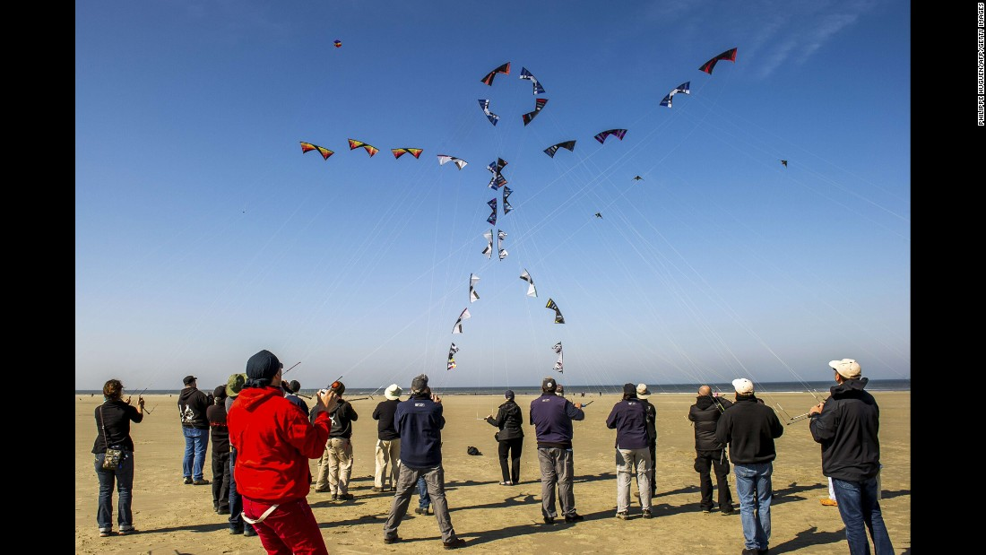 People in Berck, France, fly their kites to form the shape of a stick figure on Monday, April 20, during the annual International Kite Meeting.