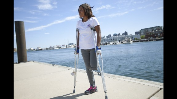 "Mery Daniel, a young mother from Haiti, was attending her second marathon when she was knocked to the pavement. She lost a leg, and the other leg was also damaged. She had pushed herself from ESL classes all the way to medical school, and instead found herself relearning how to walk with a prosthesis. She wears her ""Boston Strong"" T-shirt proudly."