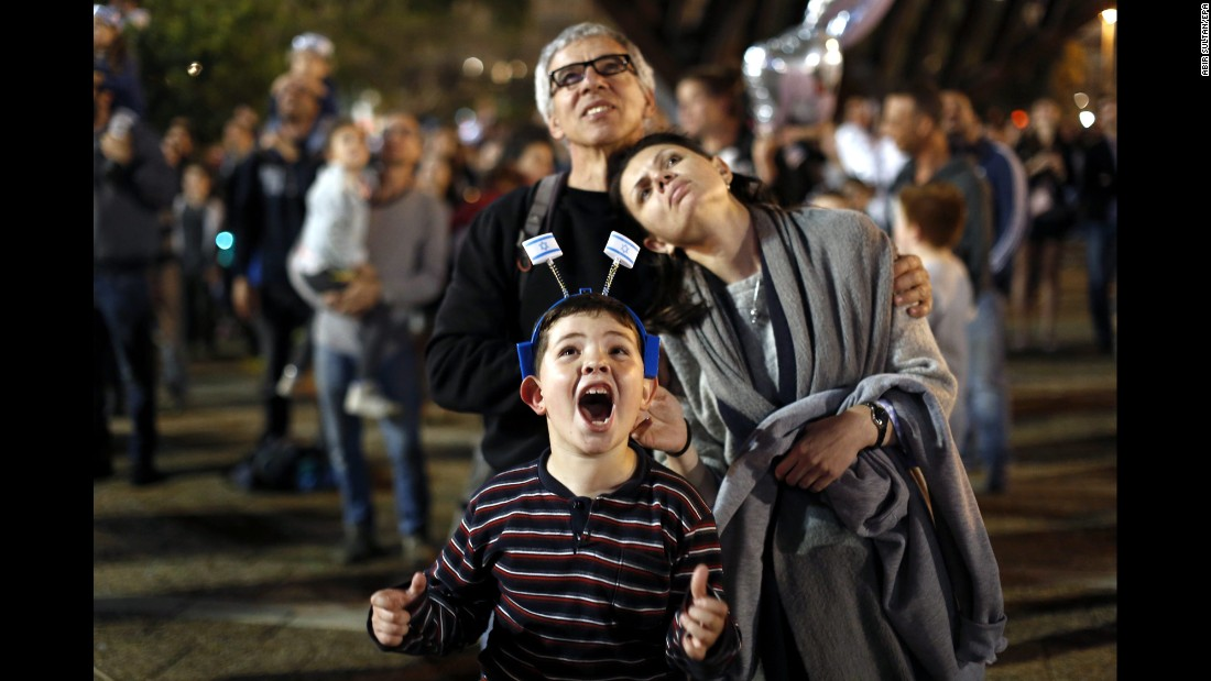 A boy watches fireworks with his parents during Independence Day celebrations in Tel Aviv, Israel, on Wednesday, April 22.