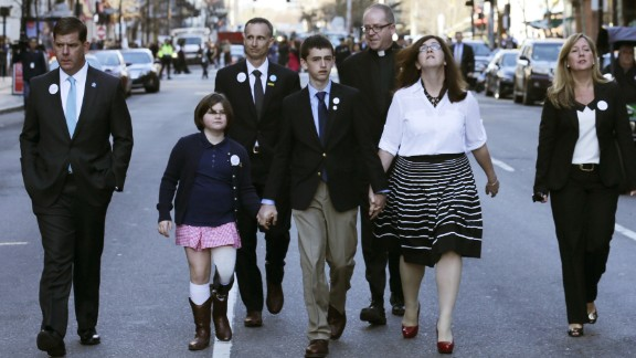 Jane Richard, in the pink skirt, lost her leg. She holds the hand of her brother Henry as they walk down Boylston Street with their parents and others after an April 15 ceremony this year. She was standing next to her brother Martin behind a metal barricade when the second bomb went off. Her father, Bill, took one look at Martin, knew he wouldn't make it and focused his efforts on saving Jane. She sang in April at Fenway Park on opening day.