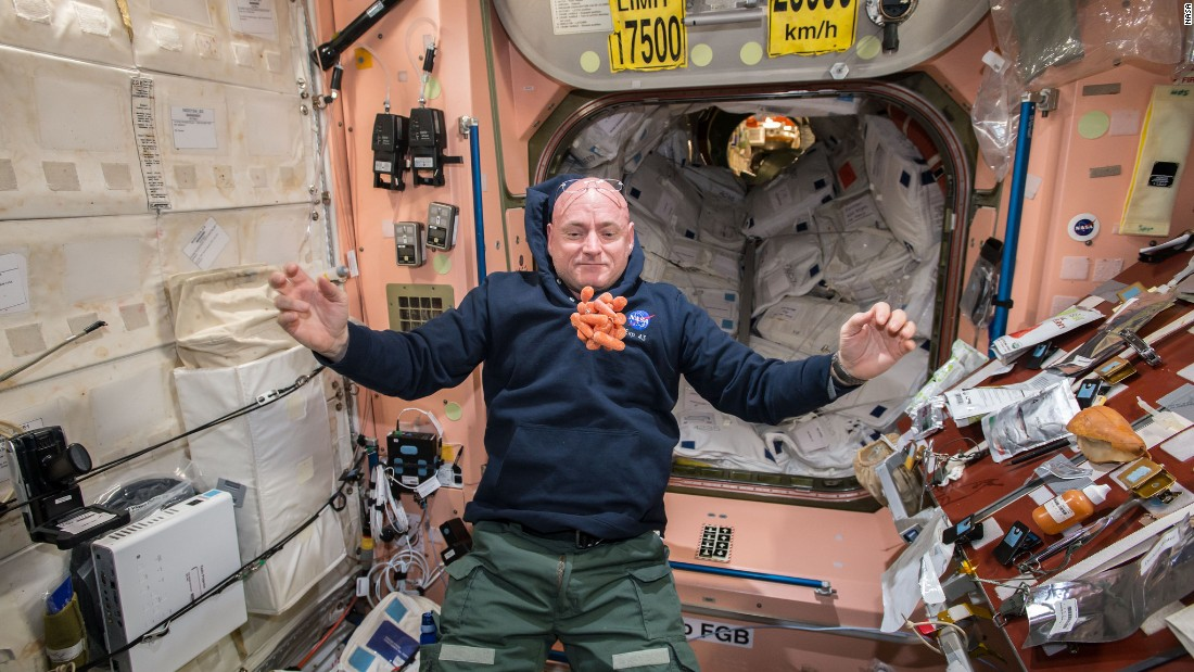 NASA astronaut Scott Kelly watches fresh carrots float in front of him on the International Space Station on Sunday, April 19. Scott is taking part in a one-year mission to test how the human body reacts to an extended time in space.
