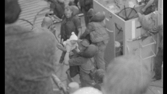 A 10-month-old Mina Nguyen cries after she is dropped into the arms of a sailor after her father's high-risk escape.