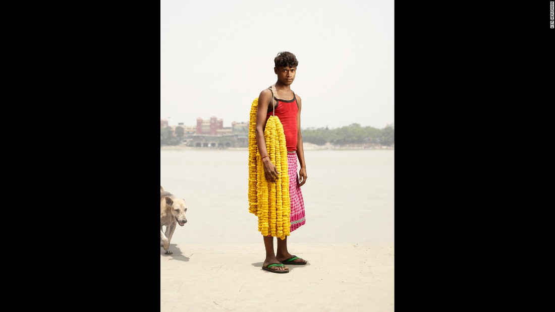 Chandan Kumar carries strands of gainda flowers on his shoulder.