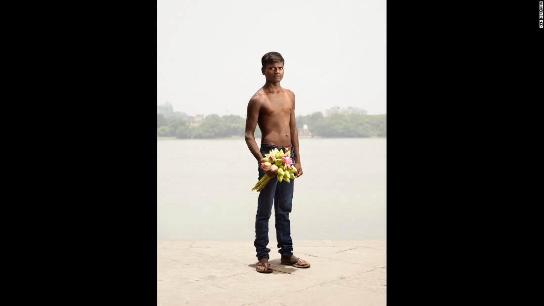 Flower seller Dev Kumar holds a bouquet of roses.
