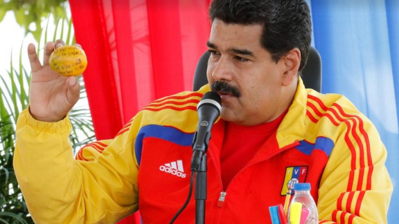 Venezuelan President Nicolas Maduro shows off the mango that a supporter threw at him.