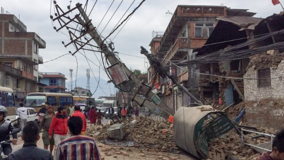 Pedestrians walk past collapsed buildings in Kathmandu on April 25.