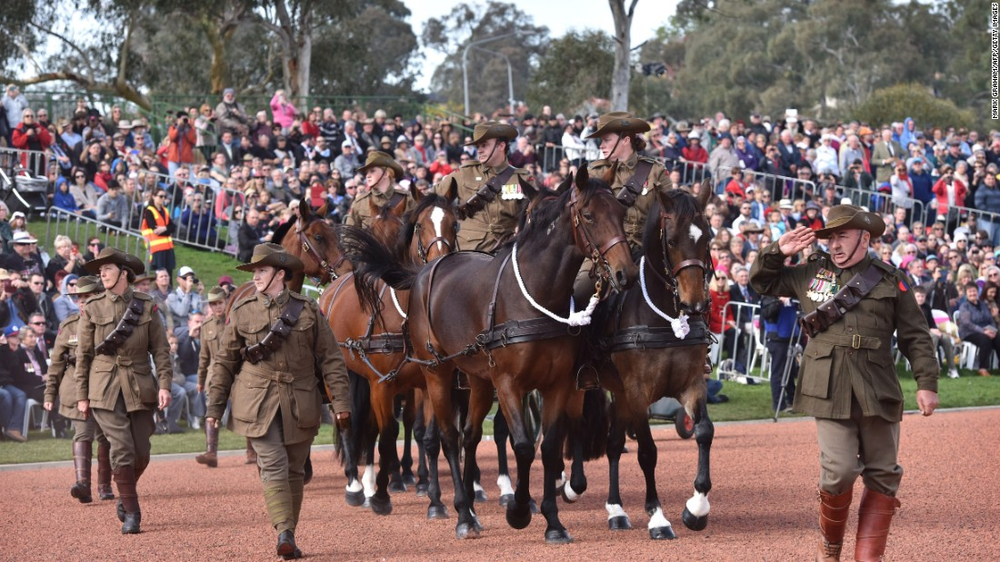 Servicemen and women march wearing period uniforms at the Australian War Memorial in Canberra, Australia.