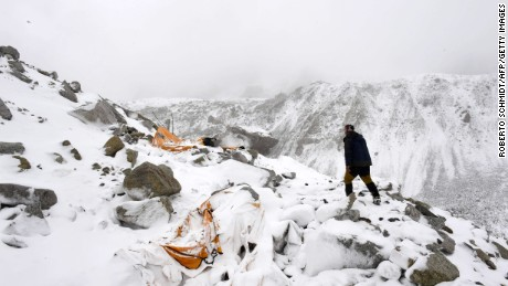 Caption:In this photograph taken on April 25, 2015, expedition guide Pasang Sherpa runs towards flattened tents in search of survivors after an avalanche that flattened parts of Everest Base Camp. Rescuers in Nepal are searching frantically for survivors of a huge quake on April 25, that killed nearly 2,000, digging through rubble in the devastated capital Kathmandu and airlifting victims of an avalanche at Everest base camp. AFP PHOTO/Roberto SCHMIDT (Photo credit should read ROBERTO SCHMIDT/AFP/Getty Images)