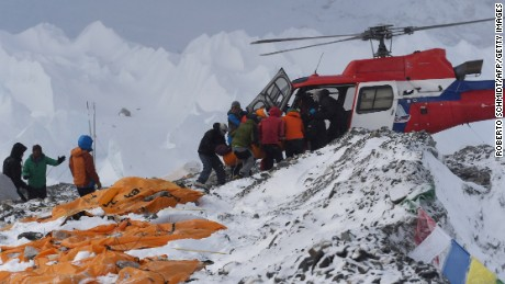 Caption:An injured person is loaded onto a rescue helicopter at Everest Base Camp on April 26, 2015, a day after an avalanche triggered by an earthquake devastated the camp. Rescuers in Nepal are searching frantically for survivors of a huge quake on April 25, that killed nearly 2,000, digging through rubble in the devastated capital Kathmandu and airlifting victims of an avalanche at Everest base Camp. The bodies of those who perished lie under orange tents. AFP PHOTO/ROBERTO SCHMIDT (Photo credit should read ROBERTO SCHMIDT/AFP/Getty Images)