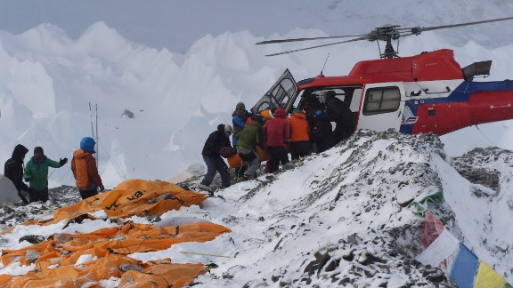 An injured person is loaded onto a rescue helicopter on Sunday, April 26, at Everest base camp. The bodies of those who died lie under orange tents. The devastating earthquake that hit Nepal on Saturday set off avalanches that left large numbers of climbers dead, missing, injured or trapped on Mount Everest.
