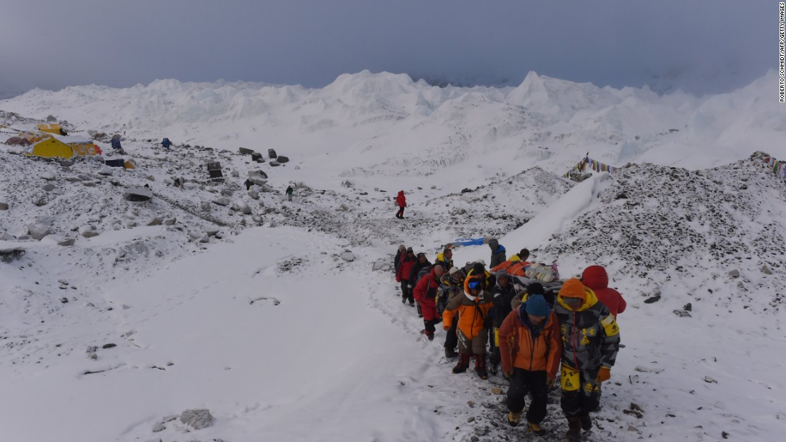 An injured person is carried by rescuers on April 26 to be airlifted by helicopter at Everest base camp.