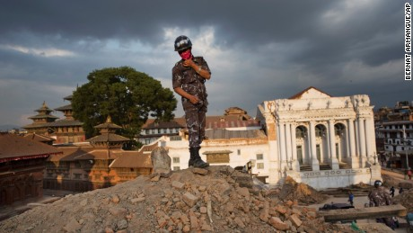 A Nepalese policeman stands atop of a rubble at Basantapur Durbar Square .