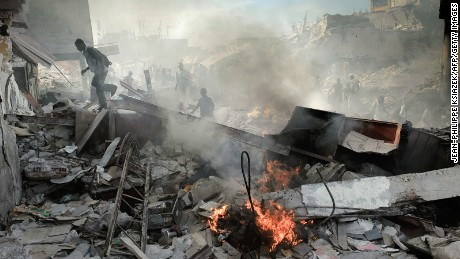 Haitians walk through collapsed buildings near the iron market in Port-au-Prince on January 31, 2010.
