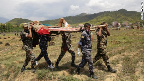Emergency personnel evacuate an injured man to a waiting helicopter in Trishuli Bazar on April 27.