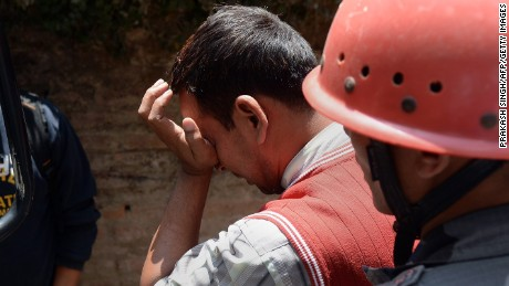A Nepalese resident reacts as police retrieve the body of his relative Prasamsah, 14, during rescue efforts in Balaju in Kathmandu on April 27, 2015. International aid groups and governments intensified efforts to get rescuers and supplies into earthquake-hit Nepal on April 26, 2015, but severed communications and landslides in the Himalayan nation posed formidable challenges to the relief effort. As the death toll surpassed 2,000, the US together with several European and Asian nations sent emergency crews to reinforce those scrambling to find survivors in the devastated capital Kathmandu and in rural areas cut off by blocked roads and patchy phone networks. AFP PHOTO/PRAKASH SINGH        (Photo credit should read PRAKASH SINGH/AFP/Getty Images)