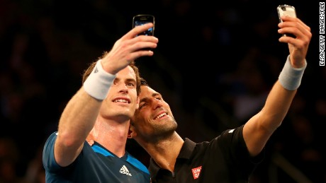Wimbledon winners Andy Murray and Novak Djokovic take selfies together.