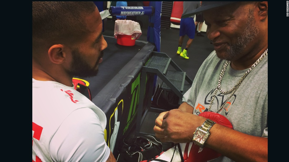 Coach Eddie Mustafa Muhammad -- former light heavyweight world champion and a veteran of 59 professional fights -- ties Theophane's gloves ahead of a sparring session in Mayweather's Las Vegas gym.