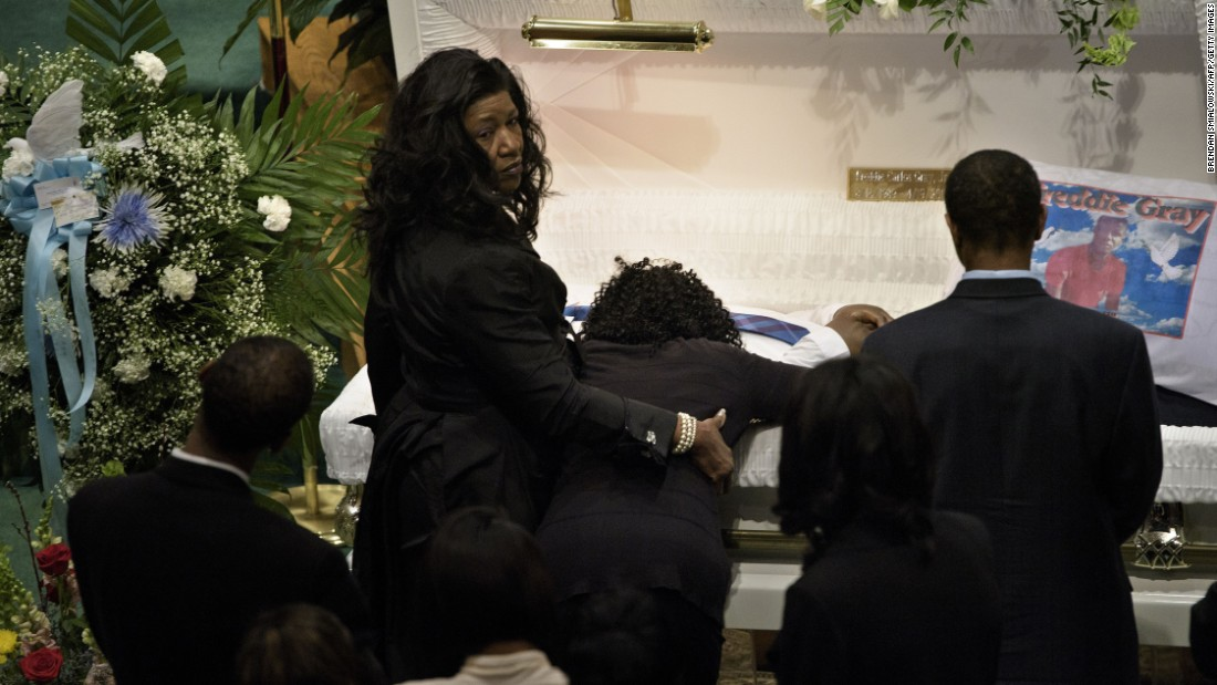 Gray's mother, Gloria Darden, kneels at his casket and embraces him before the start of the funeral.