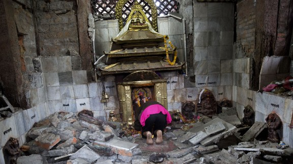 A woman prays at a ruined temple in Kathmandu on April 27.