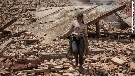 A volunteer walks on top of the debris of a collapsed temple at Basantapur Durbar Square on April 27, 2015 in Kathmandu, Nepal.