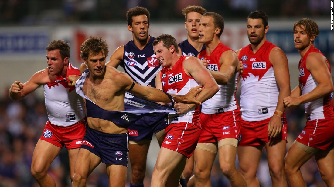 Ben McGlynn, left, and Harry Cunningham, center right, of the Swans wrestle with Matt de Boer, middle, of the Dockers during the round four Australian Football League match between the Fremantle Dockers and the Sydney Swans on Saturday, April 25, in Perth.