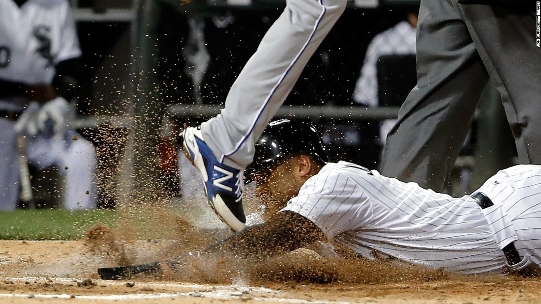 Micah Johnson of the Chicago White Sox slides into home plate under Danny Duffy of the Kansas City Royals after being tagged out by Salvador Perez (not pictured) on Friday, April 24, in Chicago.<br />