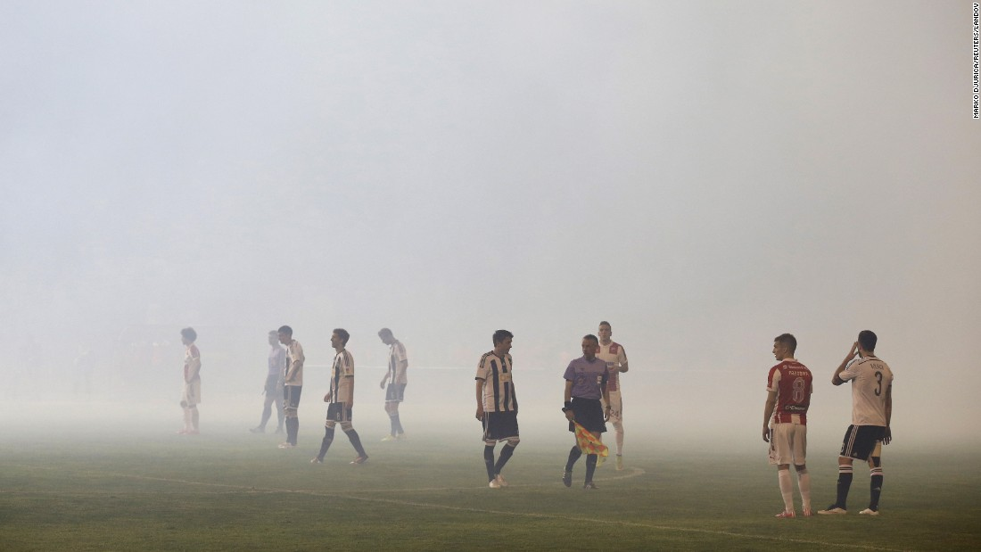 Red Star Belgrade and Partizan Belgrade players stand on the field in Belgrade, Serbia, on Saturday, April 25. The game, which ended with a 0-0 score, was delayed for 45 minutes because of crowd behavior.