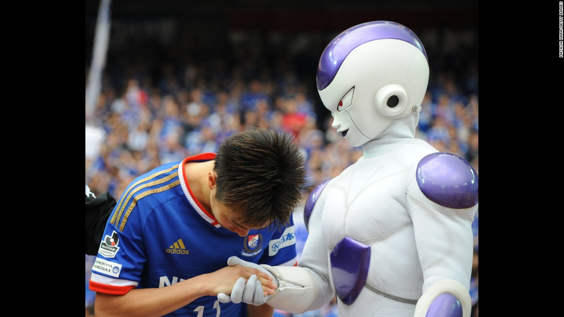 "Yokohama F. Marinos soccer player Manabu Saito shakes hands with a ""Dragon Ball Z"" character after the J. League match against Shonan Bellmare on Saturday, April 25, in Yokohama, Japan."