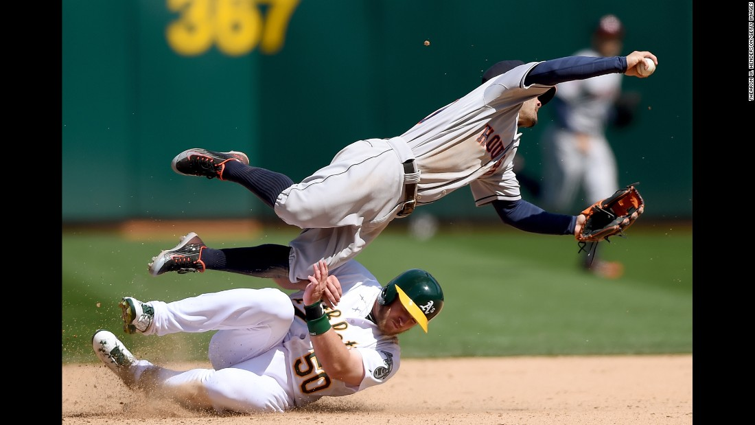 Max Muncy of the Oakland Athletics breaks up a double-play as he slides into Jose Altuve of the Houston Astros on Saturday, April 25, in Oakland, California. The Astros won the game 9-3.<br />