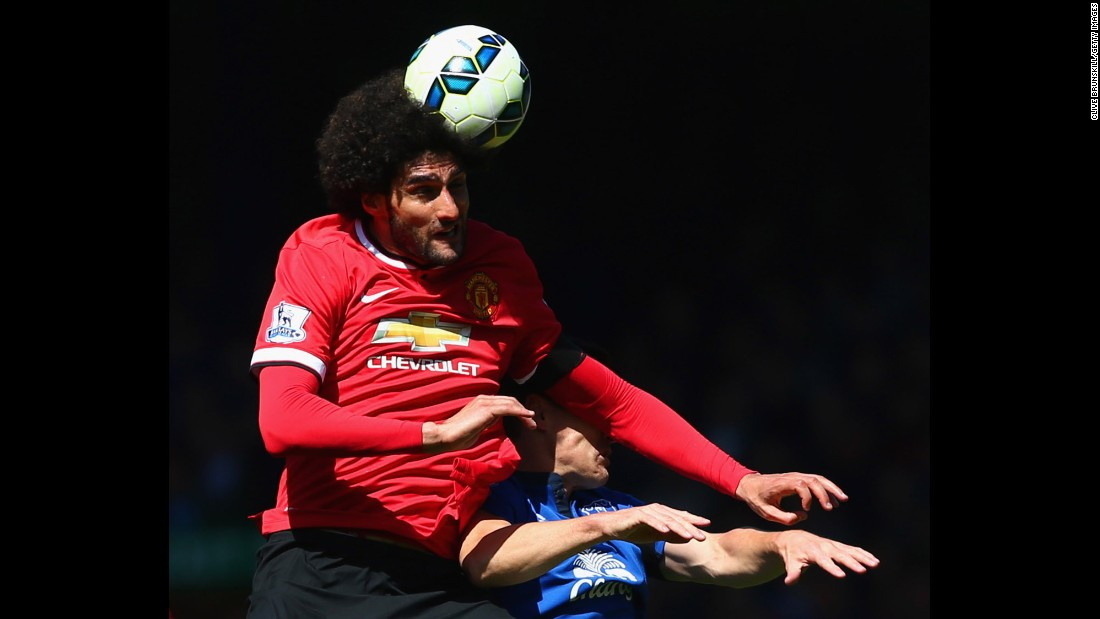 Marouane Fellaini of Manchester United heads the ball over Gareth Barry of Everton on Sunday, April 26, in Liverpool. Everton won the match 3-0.<br />