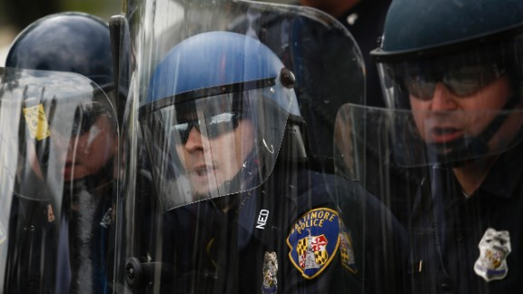 Baltimore police officers in riot gear look toward protesters near Mondawmin Mall on April 27.