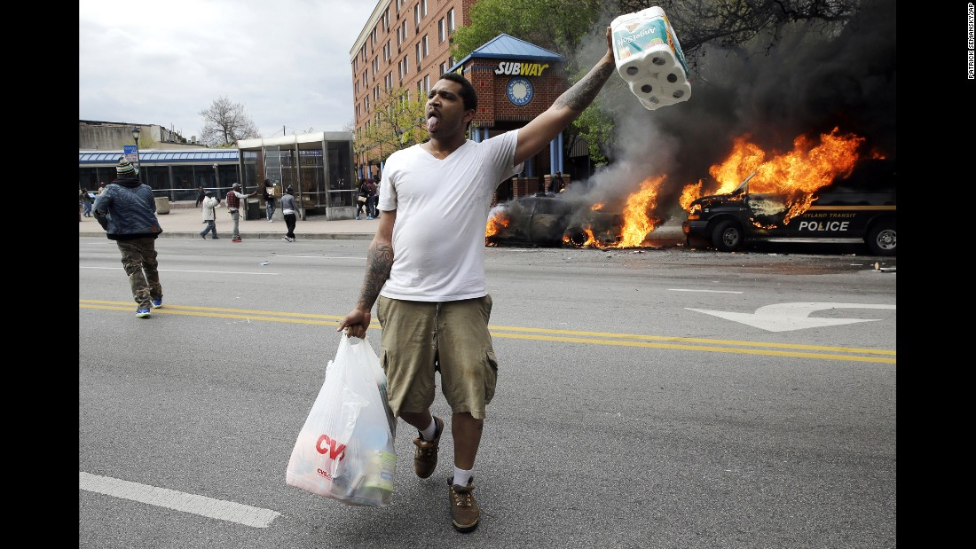 A man carries items from a store as police vehicles burn on April 27.