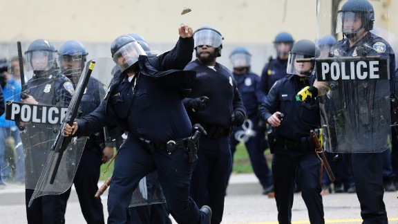 A police officer throws an object at protesters on April 27.