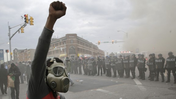A demonstrator raises his fist as police stand in formation on April 27.
