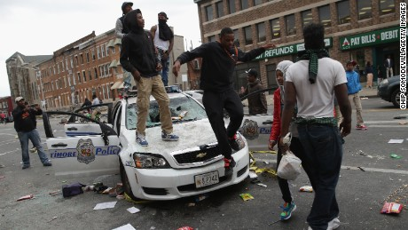 Demonstrators climb on a destroyed Baltimore Police car in the street near the corner of Pennsylvania and North avenues during violent protests following the funeral of Freddie Gray April 27, 2015 in Baltimore, Maryland.