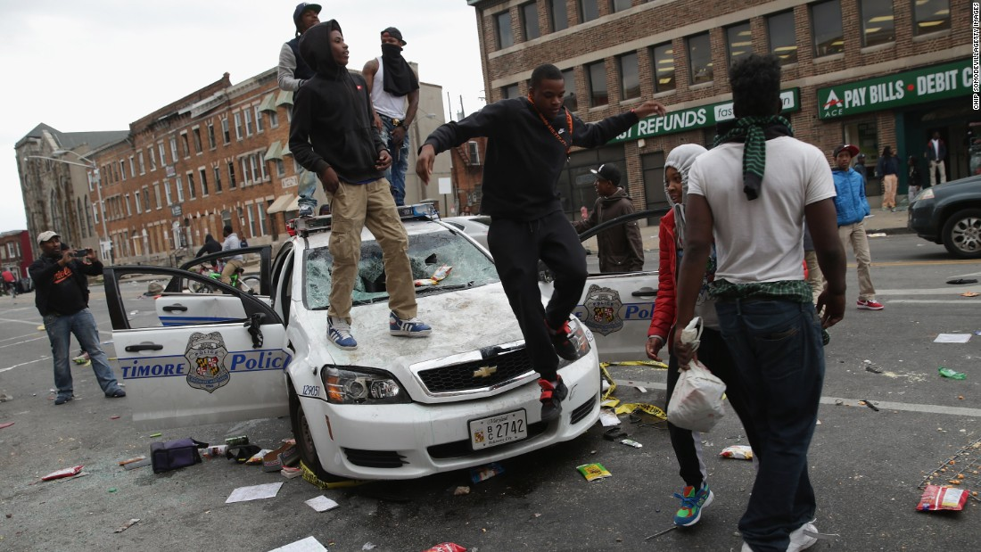 Protesters climb on a destroyed Baltimore Police car in the street near the corner of Pennsylvania and North avenues on April 27.
