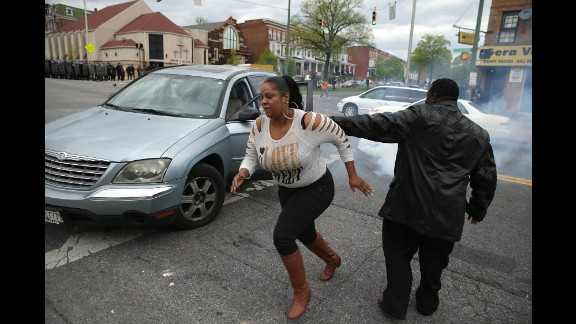 A woman abandons her car in the middle of an intersection as Baltimore Police officers clash with protesters outside the Mondawmin Mall in Baltimore on April 27.