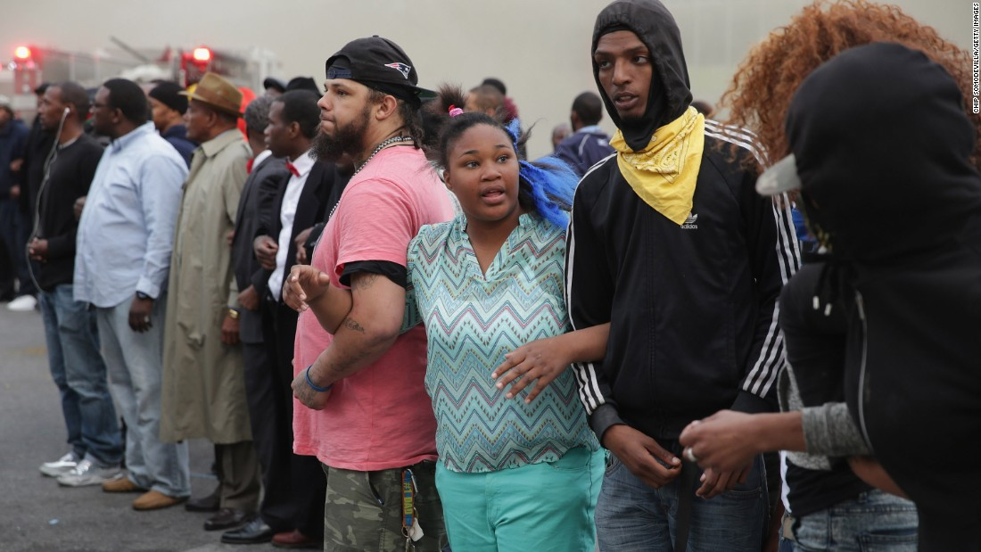 People lock arms and form a line opposing police at the corner of Pennsylvania and North avenues on April 27.