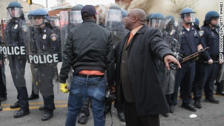 A man attempts to calm a fellow demonstrator as they face off with Baltimore police on Monday.